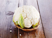 Single cauliflower on rustic wooden background — Stock Photo