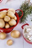 Fresh organic potatoes, rosemary and garlic over white wooden ba — Stock Photo