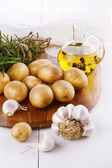 Raw organic potato with rosemary and garlic over white backgroun — Stock Photo