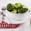 Broccoli on a white plate over white wooden background — Stock Photo #47880499