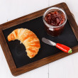 Croissant and jam on black board over white wooden background — Stock Photo #49000389