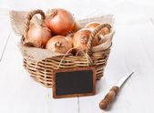 Cipolla marrone su sfondo bianco in legno — Foto Stock