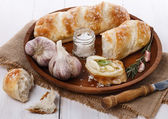 Freshly baked bread rolls and garlic — Stock Photo