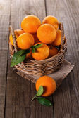 Organic oranges in a woven basket — Stock Photo
