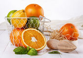 Colorful oranges, lemons and limes over white wooden background  — Stock Photo