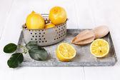 Organic lemon in vintage colander on white wooden background  — Stock Photo