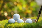 Golf balls and Driver on green grass — Stock Photo