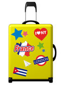 Yellow suitcase with funky stickers — Stock Photo