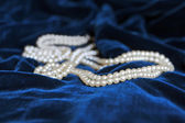 Necklace of pearls over blue velvet — Stock Photo