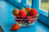 Ripe strawberry in a bowl on blue windowsill — Stock Photo