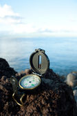 Compass at lava cliff — Stock Photo