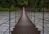 Suspension bridge above the river — Stock Photo