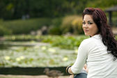 Ethnic woman sitting by a serene lake — Стоковое фото