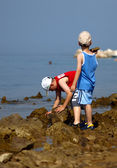 Two boys playing on a stone beach — Stock Photo
