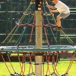 Boy climbing on monkey bars at the playground — Stock Photo #40556623