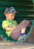 Garotinho, pensando em um tubo de madeira — Fotografia Stock