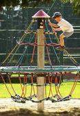 Boy climbing on monkey bars at the playground — Stock Photo