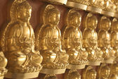 Shallow depth of field of numerous golden Buddha image — Stock Photo
