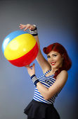 Pin up model in sailor costume holding a beach ball — Stock Photo