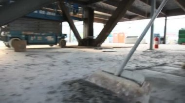 Low drifting shot of man scraping cement off floor. — Stock Video