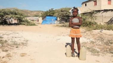 PORT AU PRINCE, HAITI - DECEMBER 17, 2013: Unidentified girl waiting with water jugs by water well in the outskirts of Port au Prince, Haiti. (For editorial use only.) — Stock Video