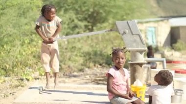 PORT AU PRINCE, HAITI - DECEMBER 17, 2013: Unidentified kids pumping water at well in the outskirts of Port au Prince, Haiti. (For editorial use only.) — Stock Video