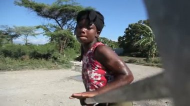 PORT AU PRINCE, HAITI - DECEMBER 17, 2013: Unidentified woman pumping water at well in the outskirts of Port au Prince, Haiti. (For editorial use only.) — Stock Video