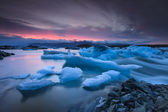 Icebergs floating in Jokulsarlon glacier lake at sunset — Stok fotoğraf