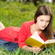 Beautiful young girl reads book in park — Stock Photo #40612777