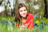Beautiful young girl laying in park — Stock Photo