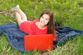 Beautiful young girl with a notebook in park — Stock Photo