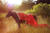 Kvinna på svart häst — Stockfoto