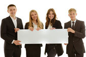 Group of four businesspersons holding a blanc banner — Stock Photo