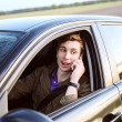 Young handsome man driving car and speaking on mobile phone — Stock Photo #47072809