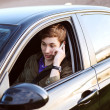 Portrait of young handsome man driving car and speaking on mobil — Stock Photo