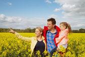菜の花畑で幸せな家族の屋外 — ストック写真