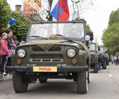 Column of military cars with veterans onboard on parade in honor — Stockfoto