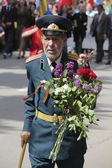 The veteran of operations with flowers on parade to the Victory — Stockfoto