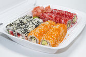 Allsorts of sushi rolls in a plastic box — Stock Photo