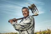 Agricultor sênior segurando o garfo de feno — Fotografia Stock