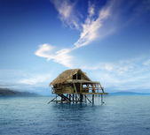 House on wooden stilts in the middle of the ocean — Stock Photo