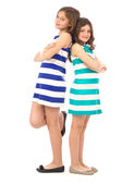 Playful sisters standing back-to-back isolated on white — Stock Photo