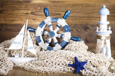 Ship and lighthouse, network with shells — Stock Photo
