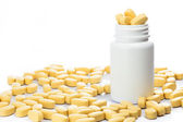 Yellow Medical pills spilling out of a medicine bottle — Photo