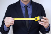 Business man with measuring tape — Stock Photo