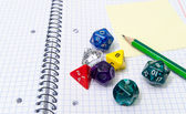 Role playing dices lying on exercise book — Stock Photo