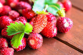 Closeup of wild strawberries on wooden table — Stock Photo