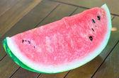 Closeup of sliced watermelon on wooden table — Stok fotoğraf