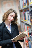 Beautiful young woman in  public library — Stockfoto
