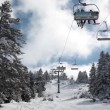 Sunny day in the snowy mountain and ski lift moves up with skiers. — Stock Video #47318351